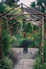 At the Heritage Home and Garden you enter under a rustic red alder arch into a garden room with a rectangular gravel patio bordered with cement tiles that have a slate-like finishing
